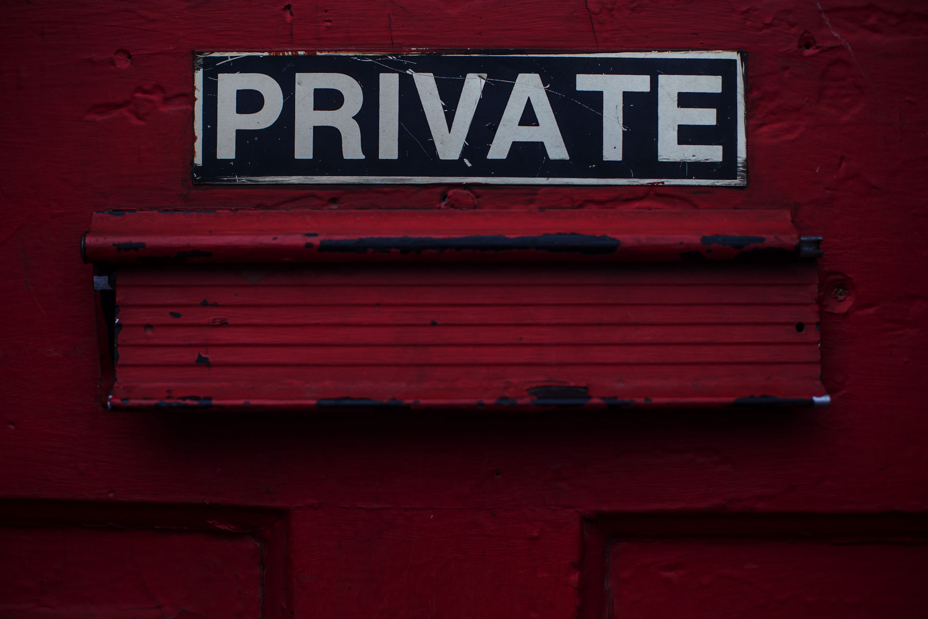 Blue and white Private sign over post slot on red door